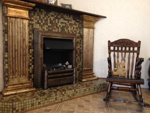 Детское кресло-качалка в интерьере гостиной у камина
